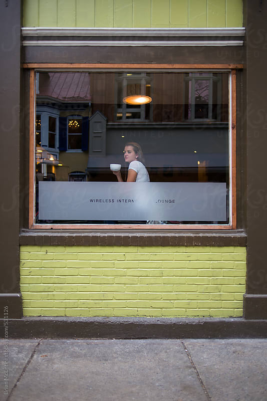 Young woman looking out of Internet cafe window by Brian McEntire for Stocksy United