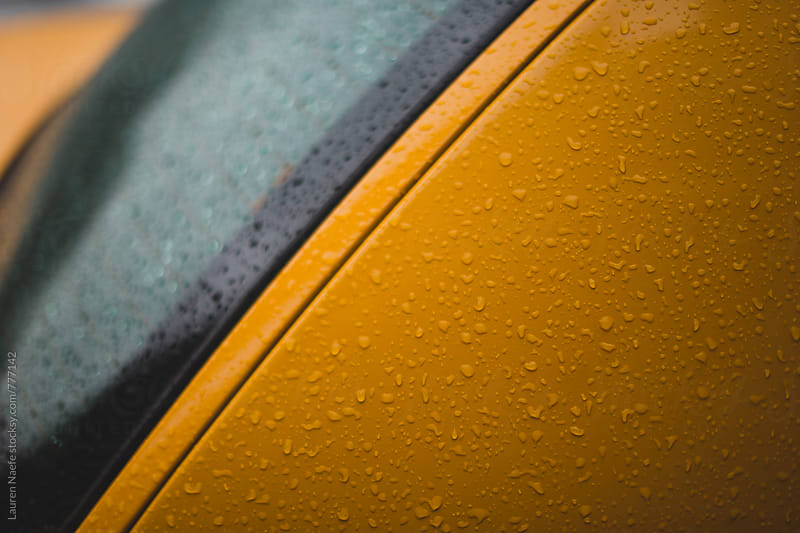 Raindrops on yellow taxi cab by Lauren Naefe for Stocksy United