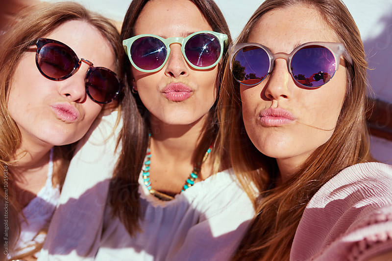 Three girls making selfie with air kiss by Guille Faingold for Stocksy United