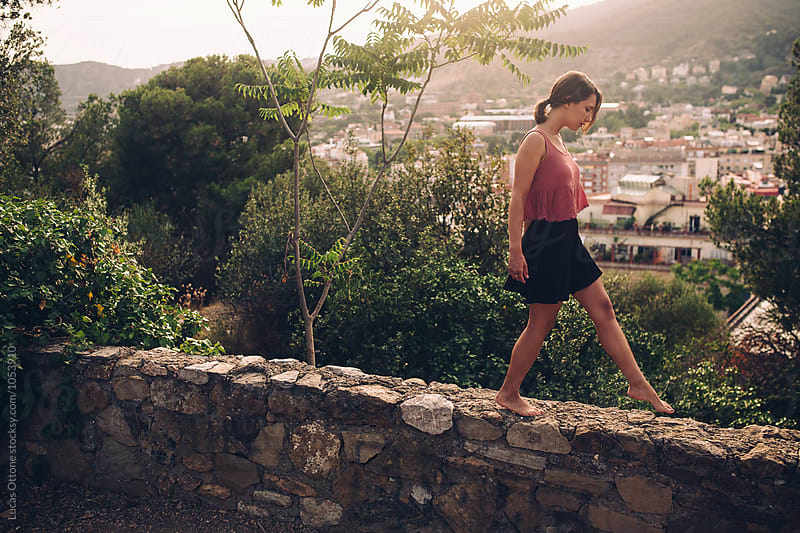 Young woman walking over a rock wall by Lucas Ottone for Stocksy United
