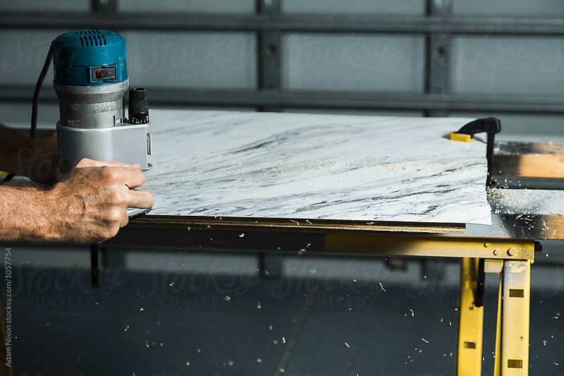 A man using a woodworking router to trim a laminate table top by Adam Nixon for Stocksy United