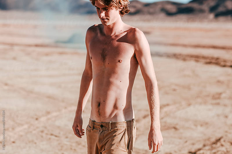 A shirtless boy stands alone in the desert sun  by HOWL for Stocksy United
