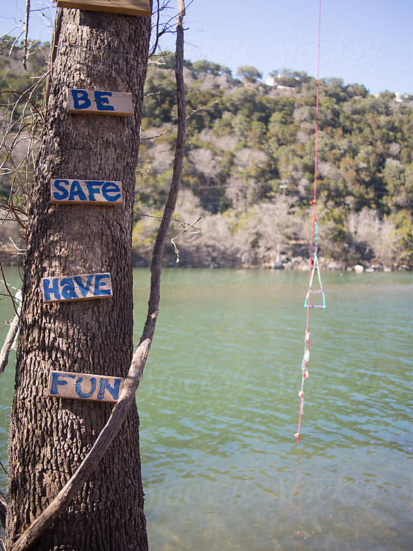 Words of wisdom on tree ladder to rope swing for water by Jeremy Pawlowski for Stocksy United