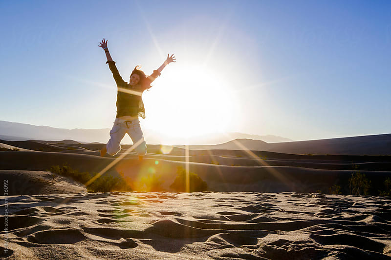 Woman Jumping on Sand Dune at Sunrise by Holly Clark for Stocksy United