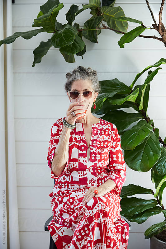 Portrait of stylish senior woman drinking cocktail by Trinette Reed for Stocksy United