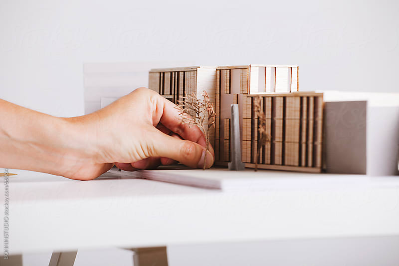 Close up of hands of young architect working on a building project with a scale model.  by BONNINSTUDIO for Stocksy United