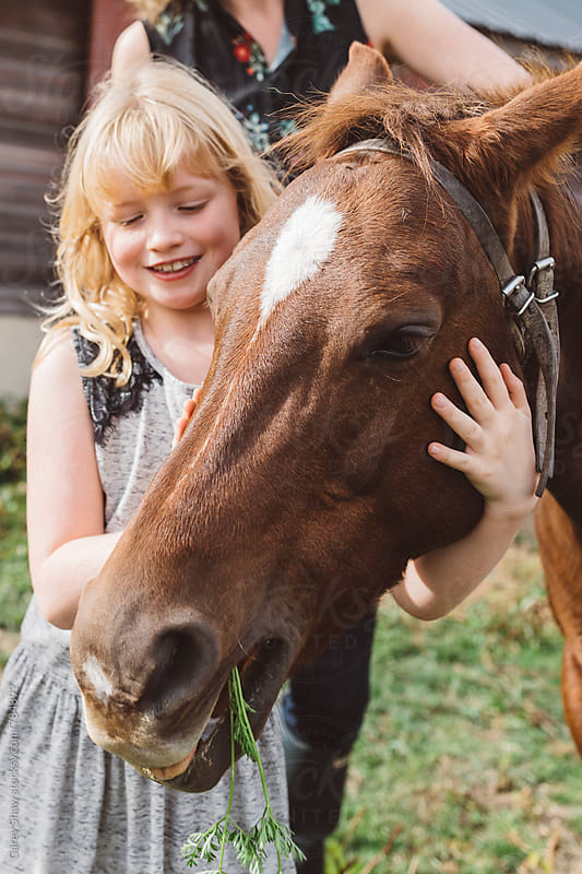 Smiling child feeding carrots to pony by Carey Shaw for Stocksy United