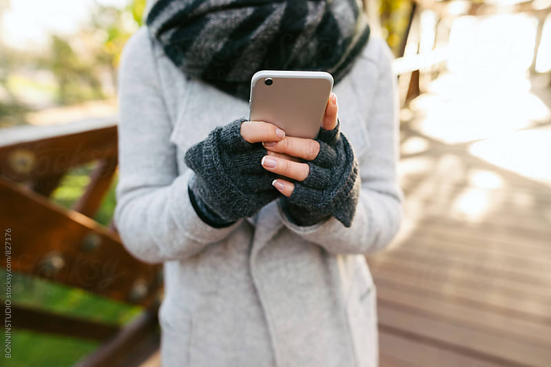 Closeup of a woman using her phone outside on winter. by BONNINSTUDIO for Stocksy United