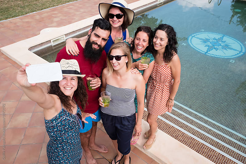 Group of friends making selfie using phone at pool by Guille Faingold for Stocksy United