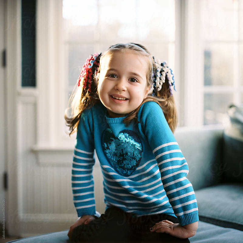 Cute young and happy girl with pigtails sitting on an ottoman by Jakob for Stocksy United