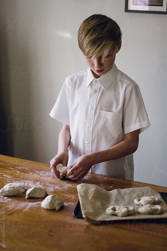 A young boy making soft pretzels by Helen Rushbrook for Stocksy United
