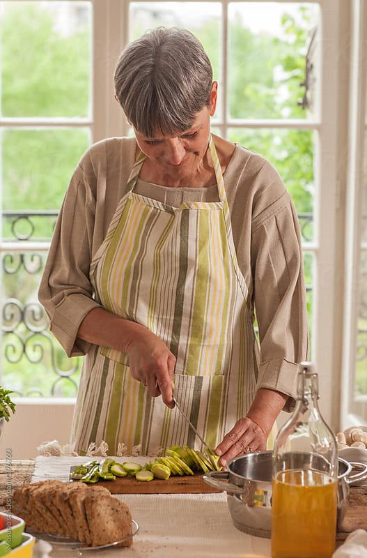 Senior Woman Cutting Veggies by Mosuno for Stocksy United