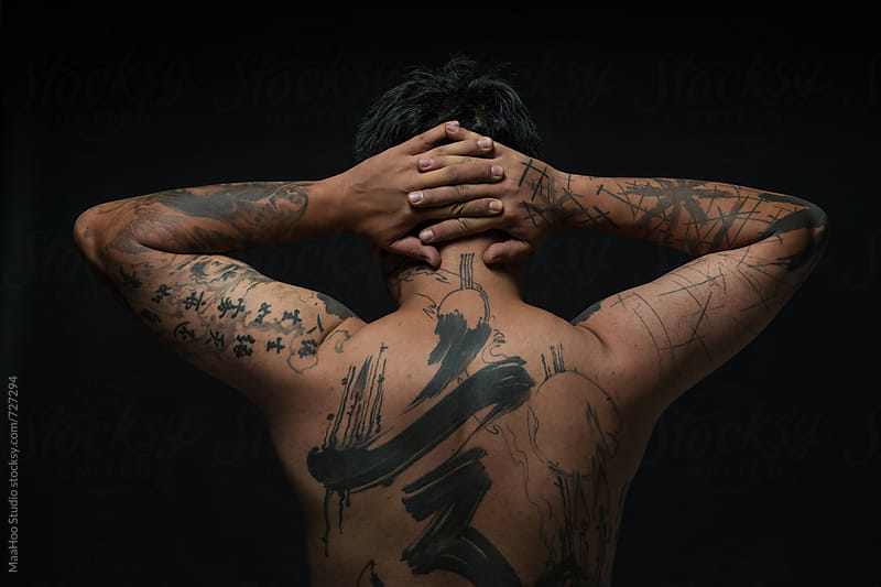 Rear view studio shot of tattooed young man with hands behind head by Maa Hoo for Stocksy United