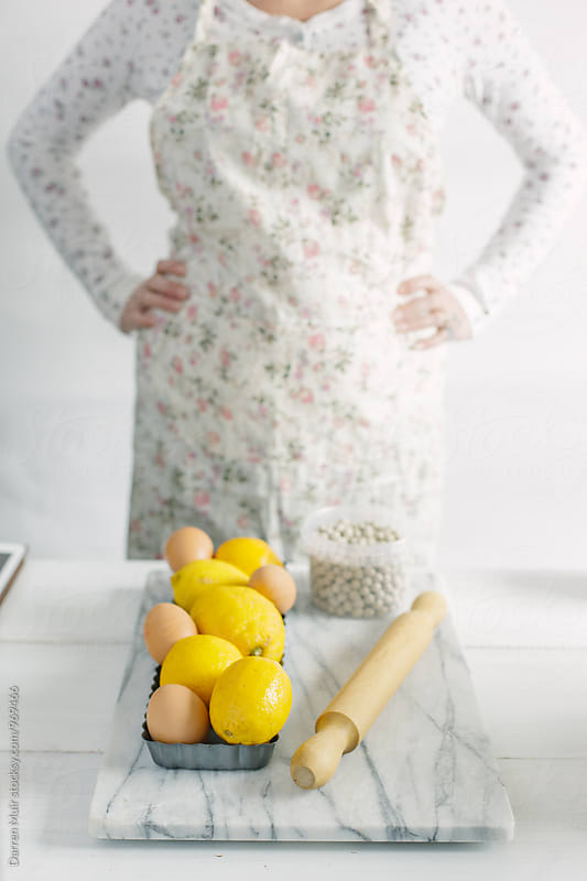Woman preparing a lemon tart: Woman standing with her hands on her hips,in front of her kitchen table. by Darren Muir for Stocksy United