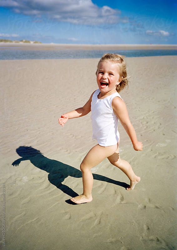 Young child running along a beach by J.R. PHOTOGRAPHY for Stocksy United