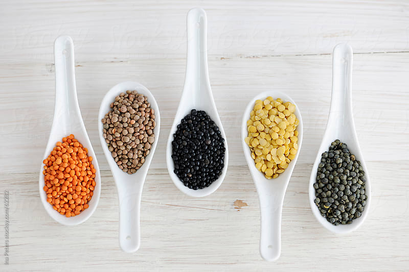 Food: Different sorts of Lentils in White Spoons by Ina Peters for Stocksy United