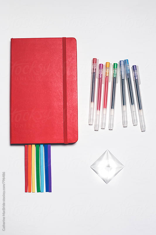 Rainbow Bookmark in red notebook with pens and prism... by Catherine MacBride for Stocksy United