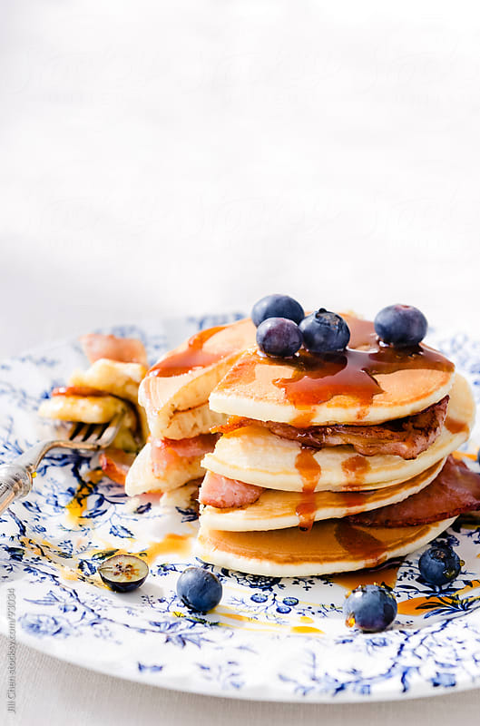 Delicious pancakes stacked with bacon and blueberries  by Jill Chen for Stocksy United