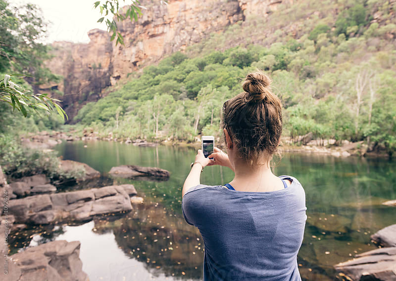 teen girl taking a photo with her cellphone at Kakadu NP, NT, Australia by Gillian Vann for Stocksy United