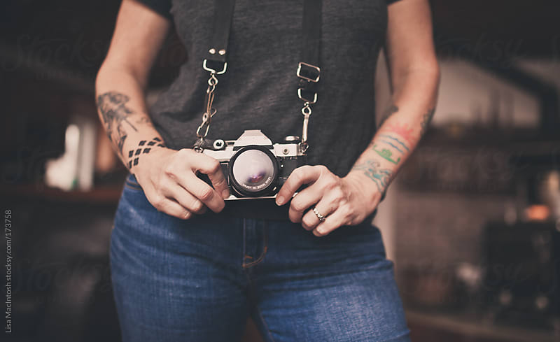 tattooed woman holding vintage camera by Lisa MacIntosh for Stocksy United