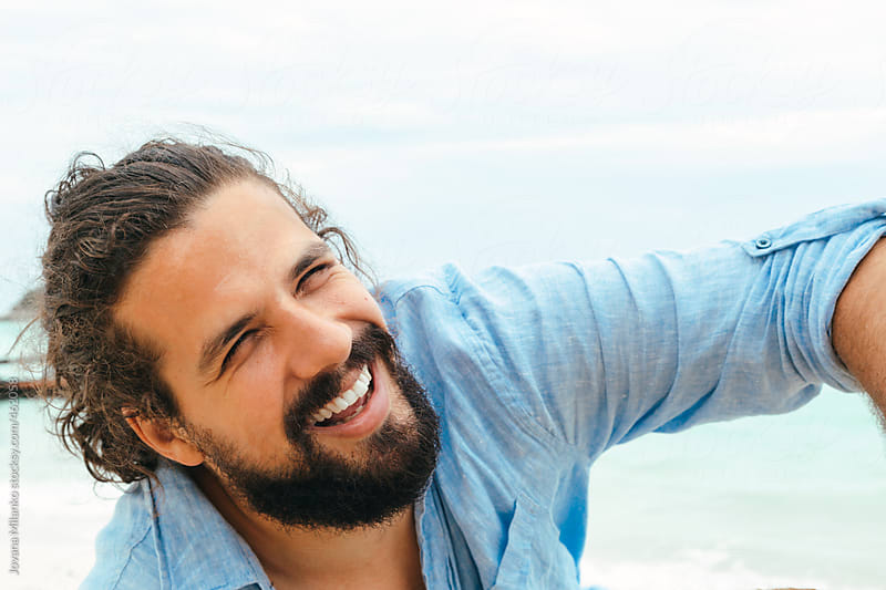Portrait of a happy, charismatic man at the beach by Jovana Milanko for Stocksy United