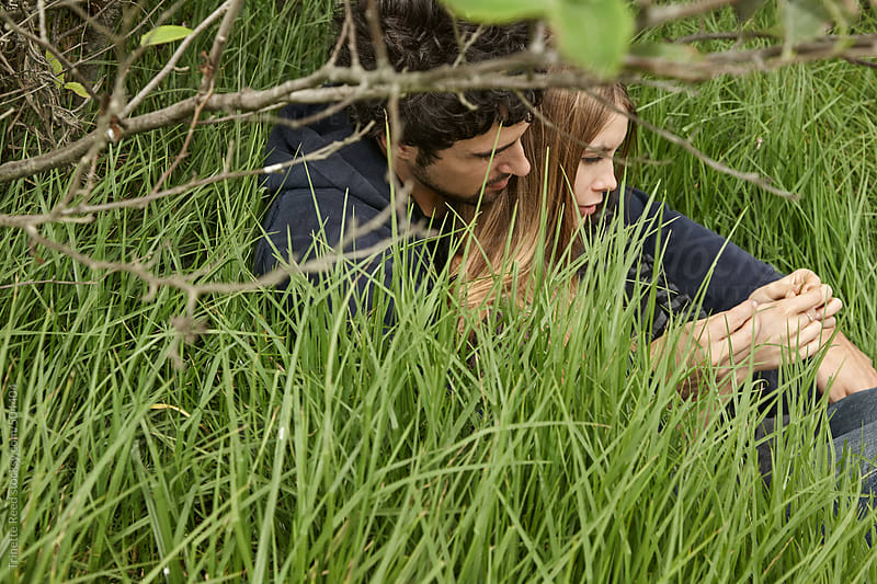 Young couple embracing in grass in nature in California  by Trinette Reed for Stocksy United