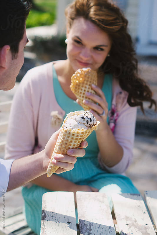 A young man holds ice cream cone while young woman smiles holding her ice cream in the background.  by Tana Teel for Stocksy United