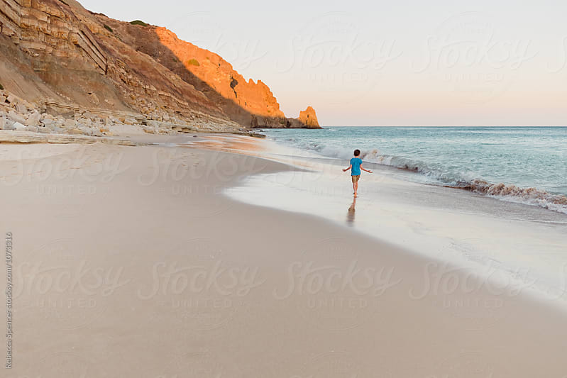 Child running along the beach at sunset by Rebecca Spencer for Stocksy United