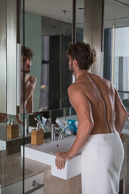 Man looking in the mirror in the morning by Jovo Jovanovic for Stocksy United