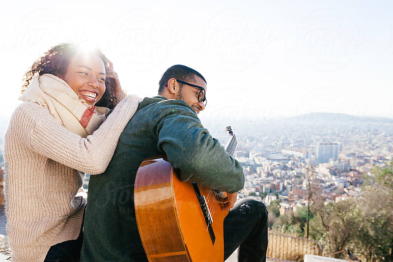 Young couple having fun above cityscape.  by BONNINSTUDIO for Stocksy United
