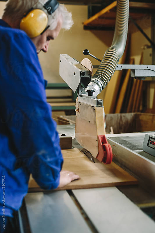 senior carpenter with yellow protection earmuffs working on a benchsaw