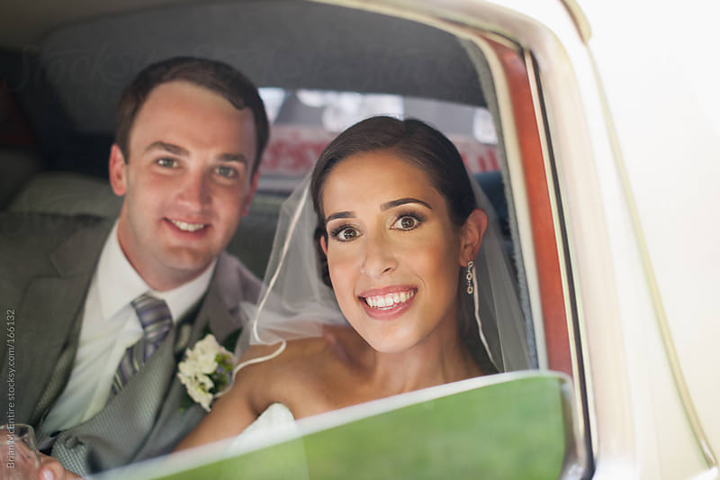 Bride and Groom in a Classic Luxury Car by Brian McEntire for Stocksy United