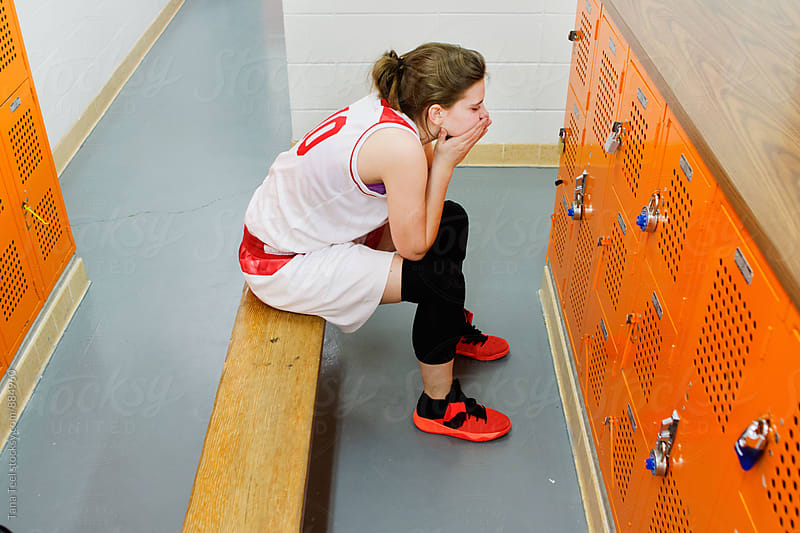 female basketball player sits in locker room by Tana Teel for Stocksy United
