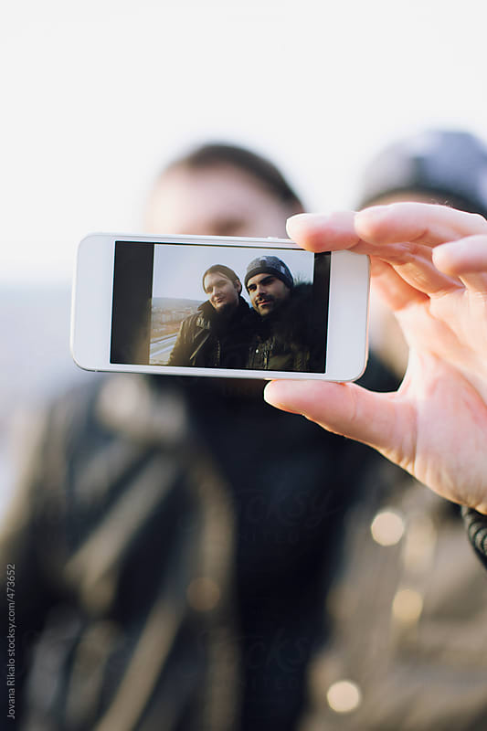 Two male friends taking self-portrait by Jovana Rikalo for Stocksy United