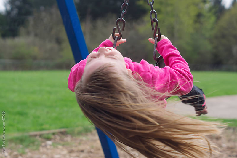Young girl twirling in a swing. by Tana Teel for Stocksy United