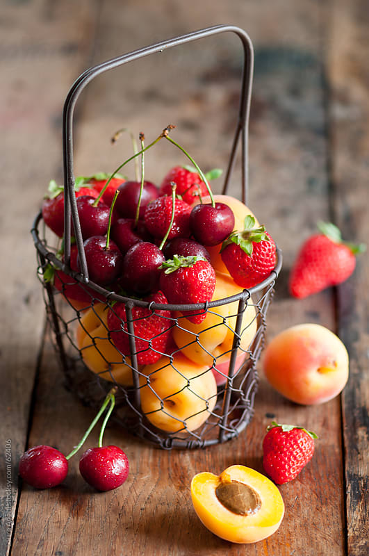 a metal basket full of summer fruit by Laura Adani for Stocksy United