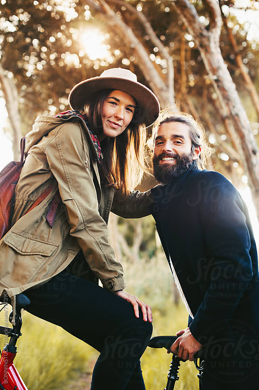 Portrait of a young couple on a bicycle in the forest. by BONNINSTUDIO for Stocksy United