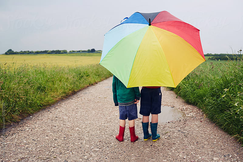 Children walking on a rainy day with a rainbow umbrella by sally anscombe for Stocksy United