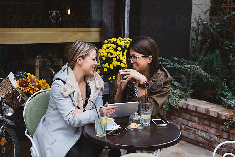 Two Female Friends Using Tablet Computer at a Cafe by Katarina Radovic for Stocksy United