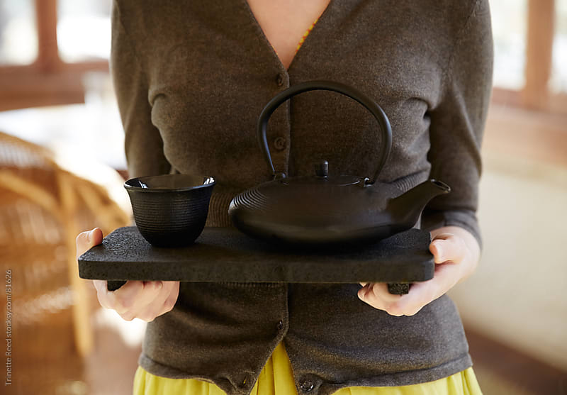 Woman carrying tray with Japanese teapot and cup on it by Trinette Reed for Stocksy United