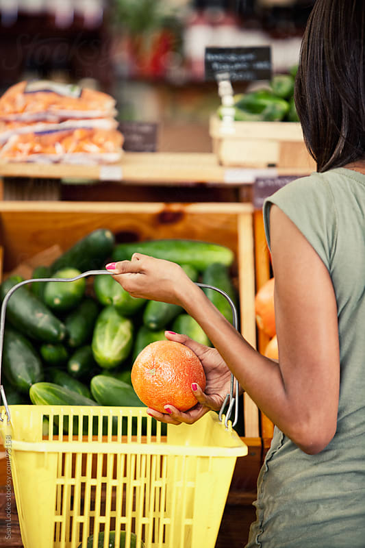 Market: Woman Puts Grapefruit Into Basket by Sean Locke for Stocksy United