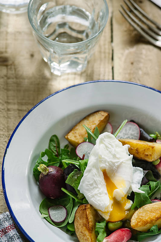 Potato salad with poached egg. by Darren Muir for Stocksy United