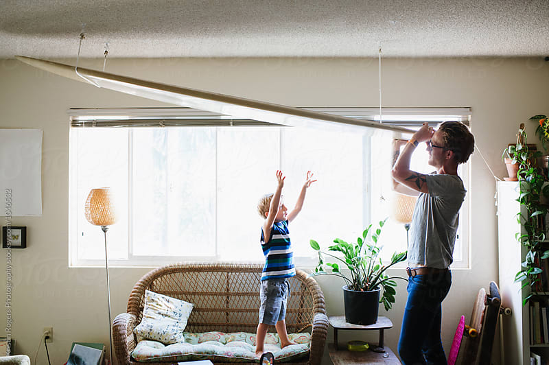 Son wanting to help dad pull down surf board by Kristin Rogers Photography for Stocksy United