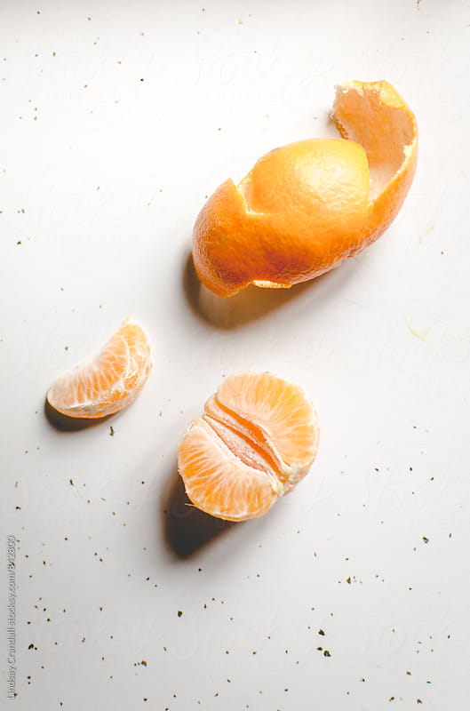 Small orange and peel on white counter by Lindsay Crandall for Stocksy United