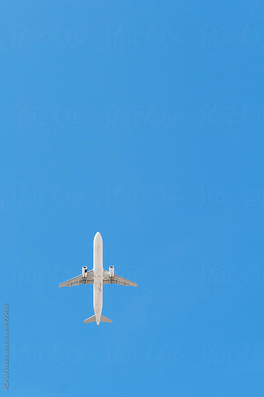 Airplane flying in the blue sky by ACALU Studio for Stocksy United