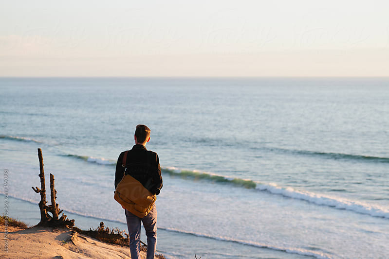 Young man looks out at ocean by Jesse Morrow for Stocksy United