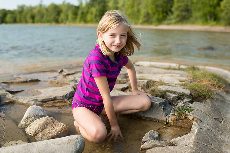 Little Girl Playing on a Rocky Northern Cottage Lakeshore on Warm Sunny Summer Day by JP Danko for Stocksy United