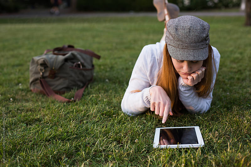 Redhead woman using her digital tablet on the grass by michela ravasio for Stocksy United