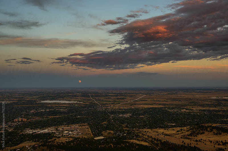 Blood Moon rising over the plains with dramaitc clouds by Mick Follari for Stocksy United