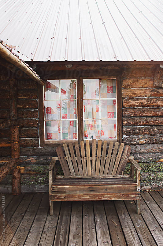 rustic wood bench in front of cabin window by Tana Teel for Stocksy United